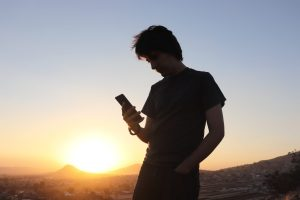 man in black t-shirt holding smartphone