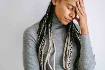 upset black woman touching head on light background