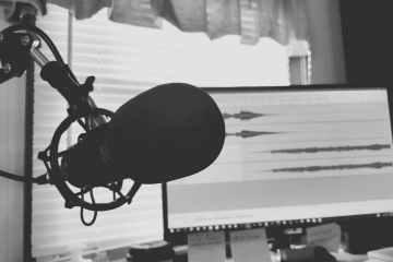 Fotografía en escala de grises del micrófono de condensador.