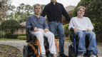 Brad Margus of Boca Raton, Fla., standing, started a company he hopes will eventually find treatments for the rare neurological disease affecting his sons Quinn, 24, at left, and Jarrett, 25. JOSH RICHIE FOR THE WALL STREET JOURNAL