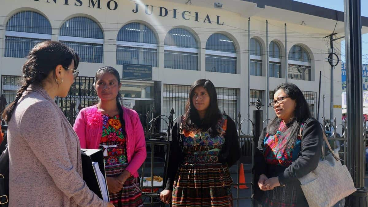 Four female members of the activist group COPA stand talking outside a court