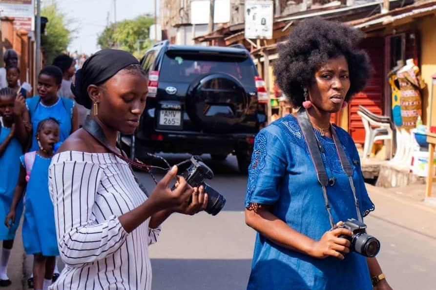 2 woman with professional cameras cross a road in Sierra Leone
