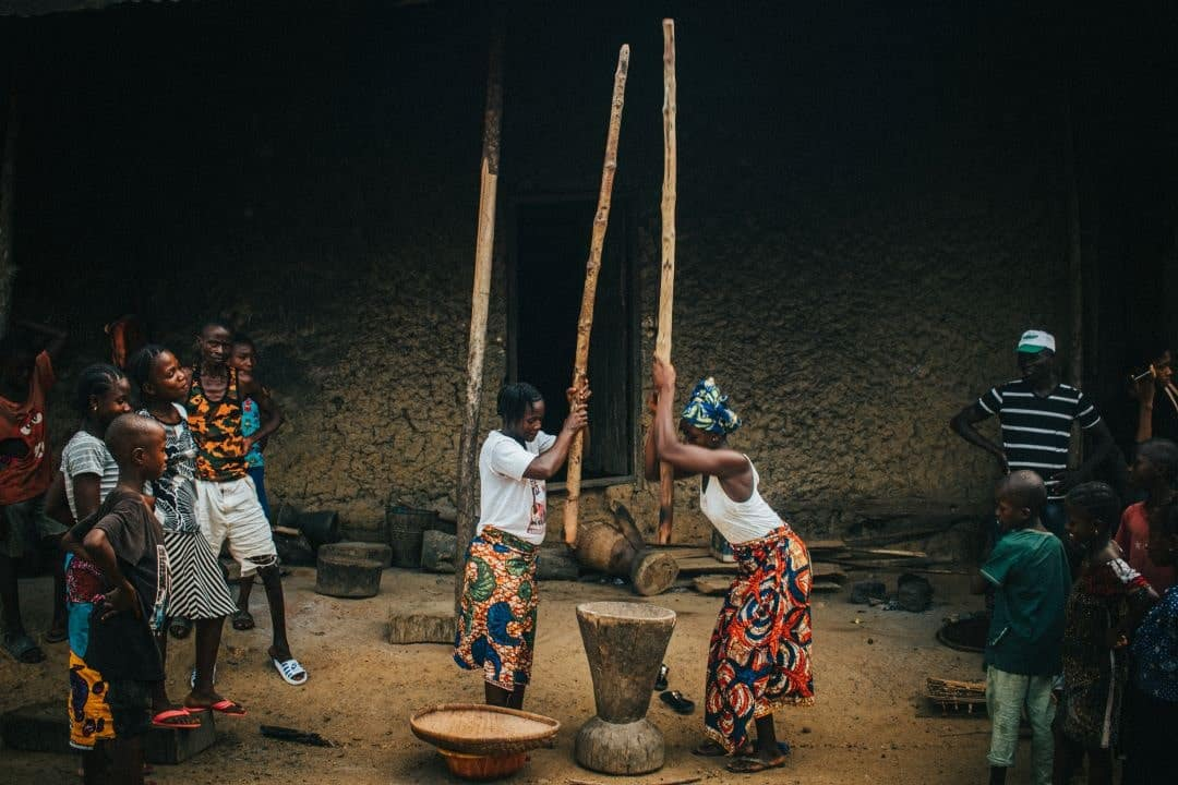2 women wearing colorful skirts pound rice with long wooden sticks