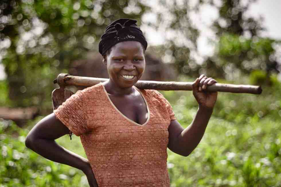 Woman in western Uganda holds a farm tool over her shoulder