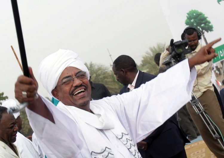Sudanese President Omar al-Bashir greets his supporters during a rally at a fair in Khartoum, Sudan, May 1, 2010. Soon after al-Bashir's election, the newspaper Suleiman worked for was closed after publishing details about an Iranian arms factory and he fled the country. (AP Photo/Abd Raouf)