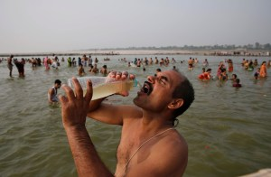 A man drinks water as Indian Hindus take dips in the holy River Ganges, June 8, 2014.  (AP Photo/Rajesh Kumar Singh)