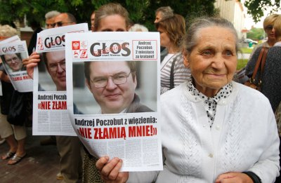 Supporters of Andrzej Poczobut, a correspondent for one of Poland's major newspapers Gazeta Wyborcza, hold papers with his portrait in front of the court building where he is on trial in the town of Grodno, Belarus, July 5, 2011. (AP Photo/Sergei Grits)
