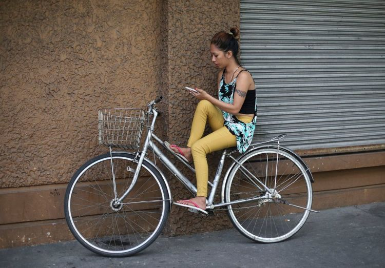 A Filipino woman sits on a bicycle as she uses her smartphone in Manila,  Jan. 28, 2015. (AP Photo/Aaron Favila)