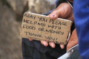 An elderly man holds a placard while begging on the streets of Harare, May 9, 2014. (AP Photo/Tsvangirayi Mukwazhi)