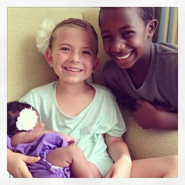Brother and sister holding newborn. transracial adoptive family. Global Munchkins