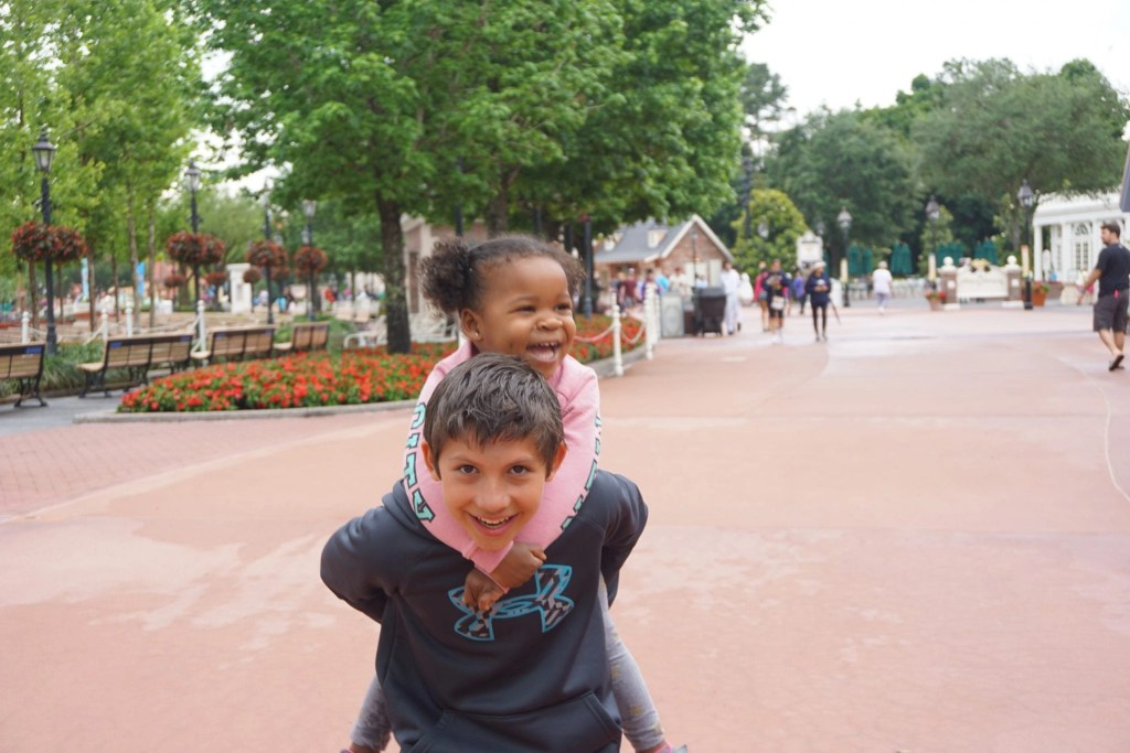 Transracial adoptive sister gets a piggy back ride from her brother in Epcot during Disney SMMC | Global Munchkins