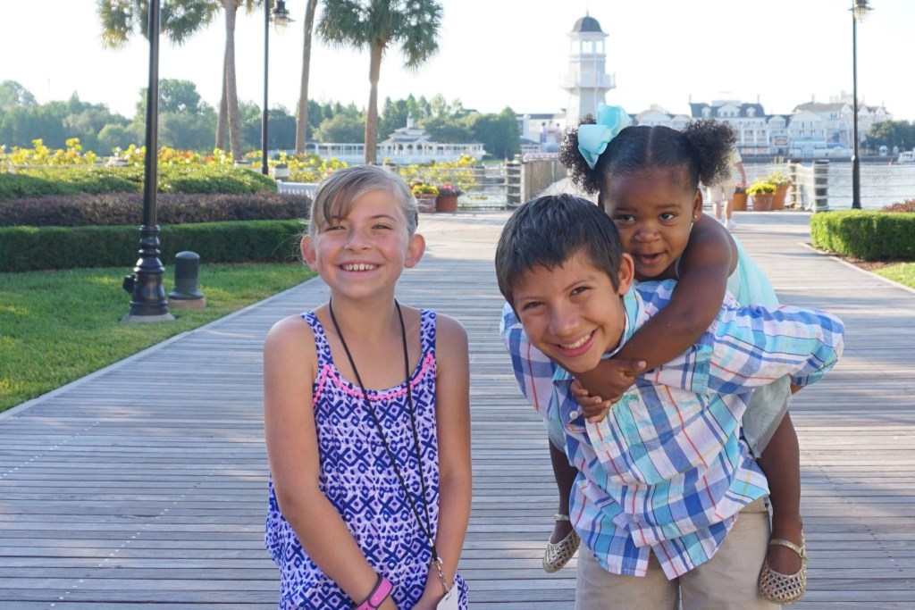 Mutli-Cultural Family on boardwalk in front of lighthouse at Disney's Yacht Club Resort | Global Munchkins