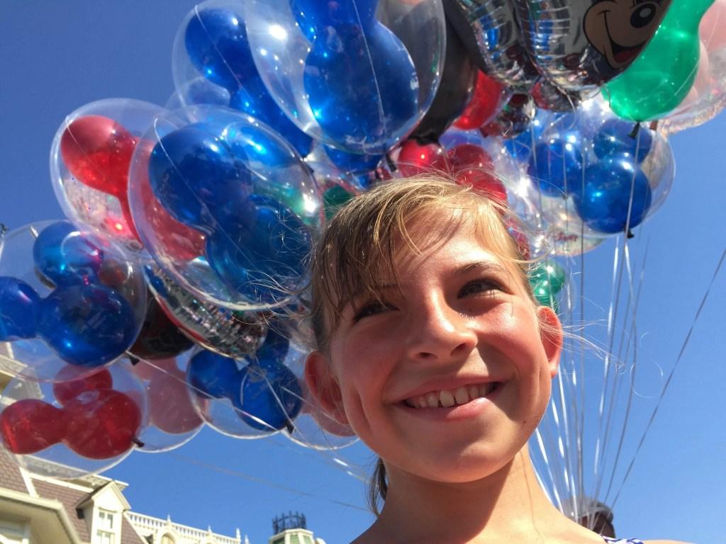 Disney World Tips - Happy Girl with Mickey Balloon Background at Magic Kingdom | Global Munchkins