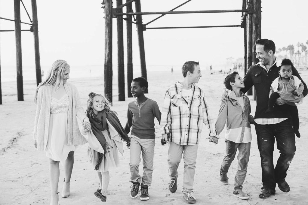 Transracial adoptive family Family walking on beach | Global Munchkins