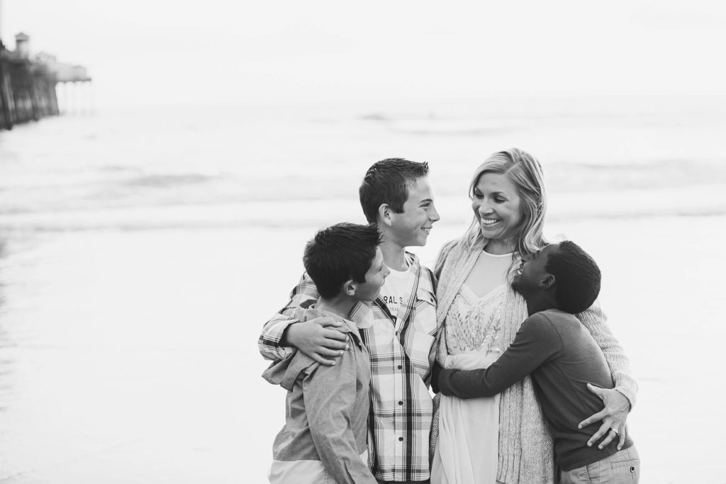 "Being ""mom enough"" A black and white photo of a mother embracing her adopted and biological sons on a beach 