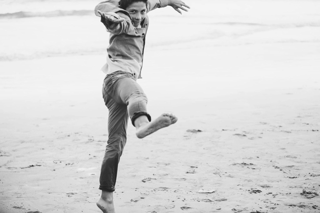 Boy jumping on beach | Global Munchkins