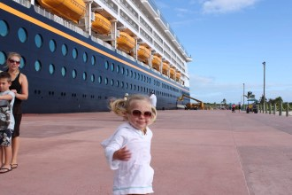 Little girl with pigtails running with Disney Cruise Ship in background | Global Munchkins