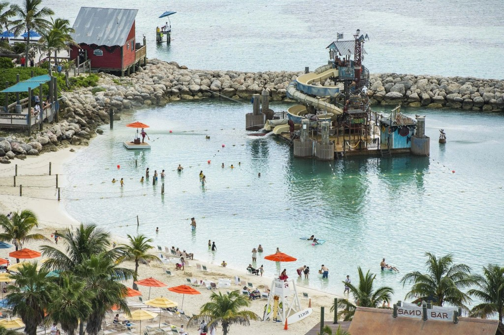 """Guests slide and splash on Pelican Plunge, an exciting water play area located within swimming distance from the shore at Castaway Cay. The 2,400-square-foot floating platform has two water slides—an enclosed corkscrew slide and a 140-foot-long open slide—that take guests on a twisting ride, ending with a splash into the lagoon. A giant """"bucket dump"""" and water cannons soak guests on the platform. (Matt Stroshane, photographer)"""