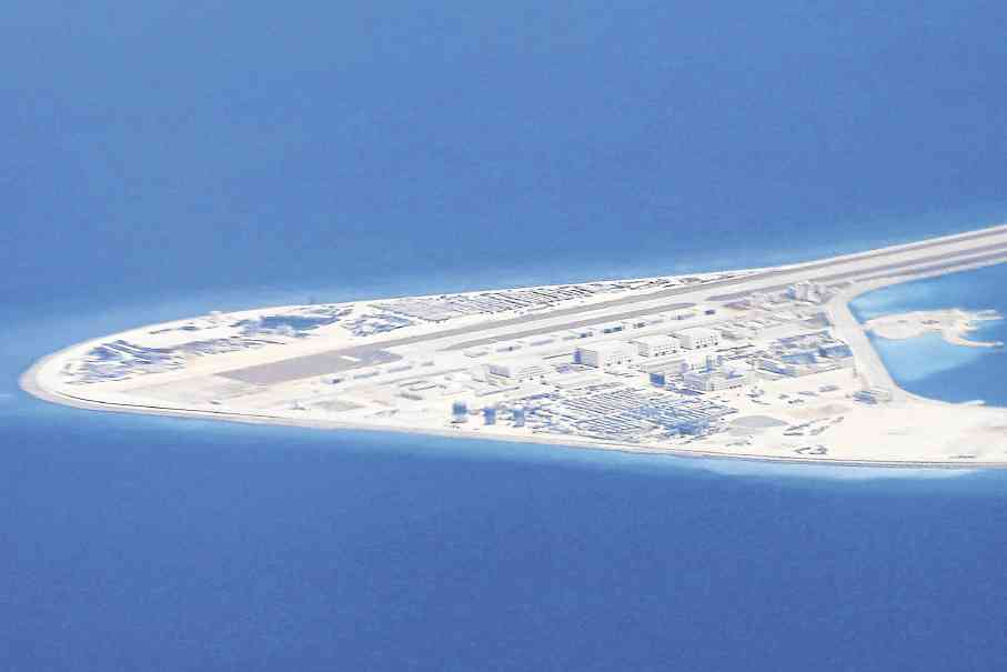 Chinese structures and an airstrip on the man-made Subi Reef at the Spratly archipelago in the South China Sea are seen from a Philippine Air Force C-130 transport plane on Friday. —AP