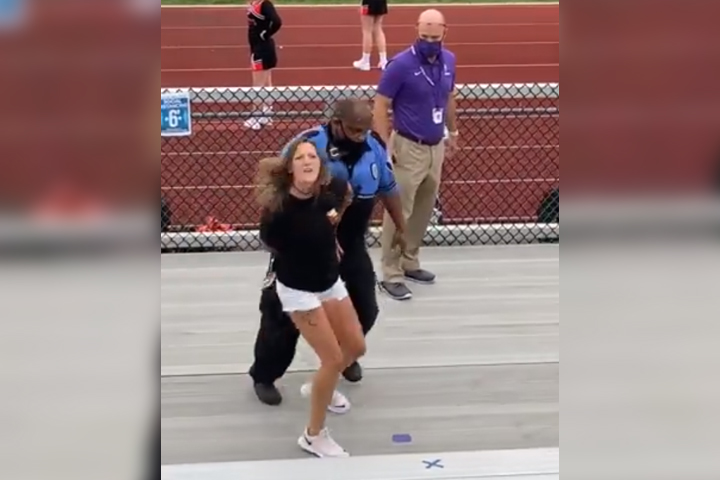 A police officer leads a woman out of the bleachers in at Logan High School in Logan, Ohio, on Sept. 23, 2020.