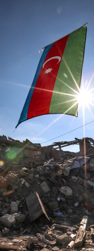 Azerbaijan's national flag flies over destroyed houses in a residential area that was hit by rocket fire overnight by Armenian forces, on Oct. 22, 2020 in Ganja, Azerbaijan's second largest city, near the border with Armenia.