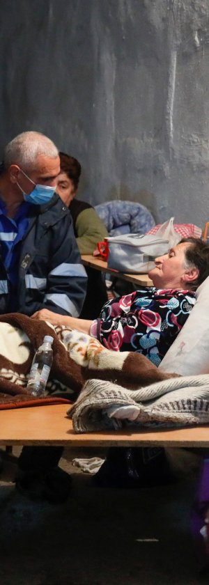 A medical worker talks to a sick woman in a bomb shelter in Stepanakert, the separatist region of Nagorno-Karabakh, Oct. 22, 2020.