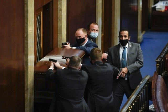 U.S. Capitol Police with guns drawn stand near a barricaded door as protesters try to break into the House Chamber at the U.S. Capitol on Wednesday, Jan. 6, 2021, in Washington.