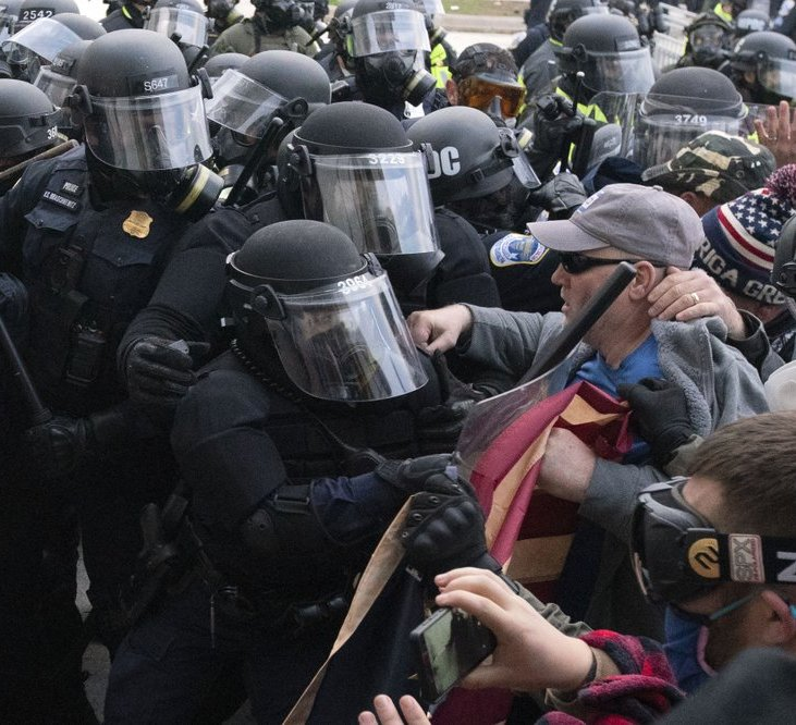 Capitol police officers in riot gear push back demonstrators who try to break a door of the U.S. Capitol on Wednesday, Jan. 6, 2021, in Washington.
