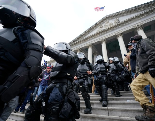 Police in riot gear walk out of the Capitol, Wednesday, Jan. 6, 2021, in Washington. – AP Photo/Manuel Balce Ceneta