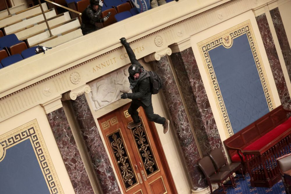 A protester is seen hanging from the balcony in the Senate Chamber on January 06, 2021 in Washington, D.C.