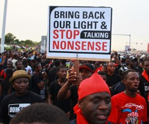 In this photo taken on Saturday, May 16, 2015, people protest against power cuts by carrying banners one reading, 'Bring back our lights and stop taking nonsense' in  Accra, Ghana. Ghana's movie stars have joined blue-collar workers in demonstrations against power cuts, marching through the streets of the capital to demand an end to this West African nation's ongoing energy crisis.
