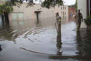 Lt. Norman Beauregard (L) and firefighter Kevin Attender, both with the Georgetown Fire Department, check out flooded Front Street in Georgetown, South Carolina October 4, 2015. REUTERS/Randall Hill