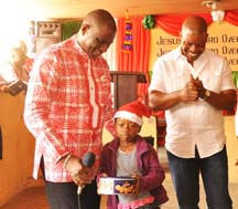 Managing Director and Chief Executive Officer, Airtel Nigeria, Segun Ogunsanya; kid of Arrow of God Orphanage, Chioma Emmanuel with Director of the orphanage, David Ogo-Tsegah during the visit of Airtel employees to the home at Ajah, Lagos on Tuesday.