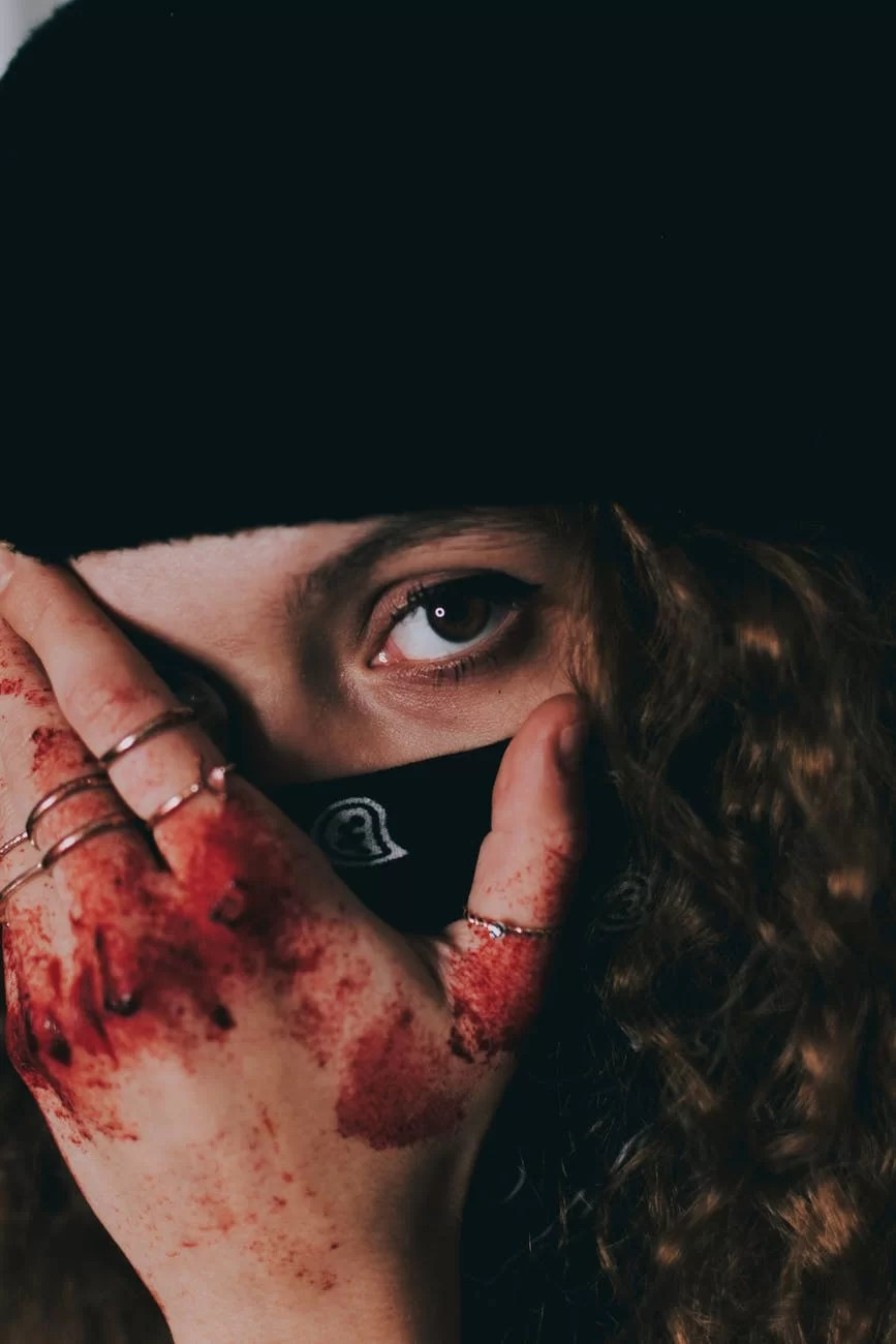 woman in mask with blood on hand