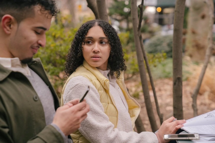 latin american couple at table with textbooks with smartphones