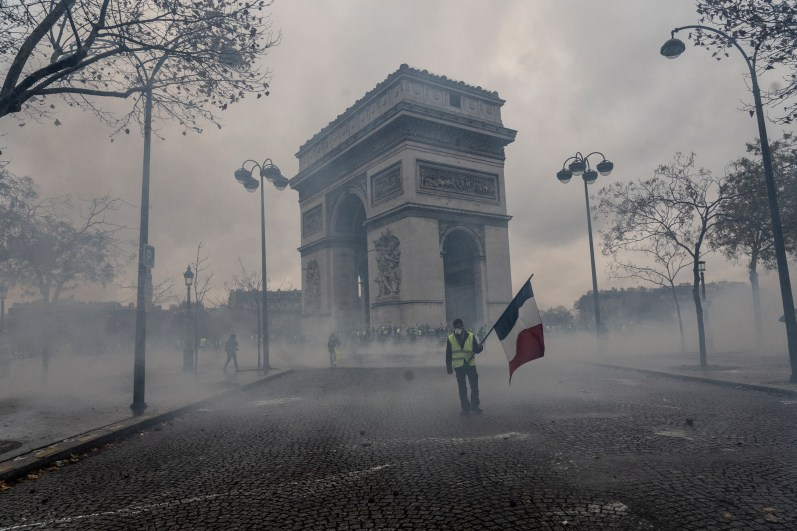"""PARIS, FRANCE - DECEMBER 01: Fightings between police and the """"gilets jaunes"""" on the Place de l'Etoile in front of the Arc de Triomphe, on December 1, 2018 in Paris, France. The demonstrators, known as """"gilets jaunes"""" or """"yellow vests,"""" have protested across France for the last two weeks, demanding a reduction in fuel prices. French law requires drivers to carry yellow vests in case of accident. (Photo by Veronique de Viguerie/Getty Images)"""