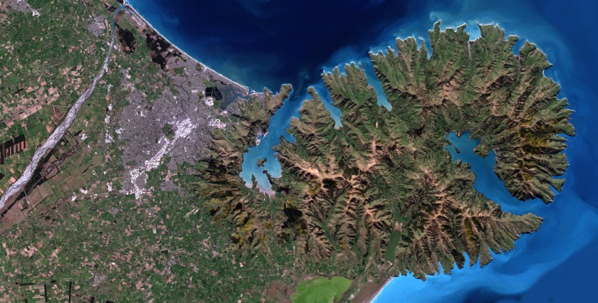 This satellite image shows Banks Peninsula, including Lyttelton Harbour and Akaroa Harbour, and the city of Christchurch, in Canterbury, New Zealand.