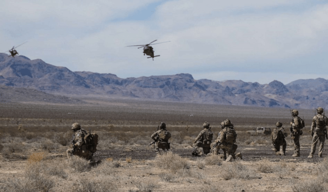 U.S. Special Forces Soldiers and Airmen from the 99th Civil Engineer Squadron EOD team and 66th Rescue Squadron, watch as two UH-60 Blackhawk helicopters land at the Nevada Test and Training Range, Nevada