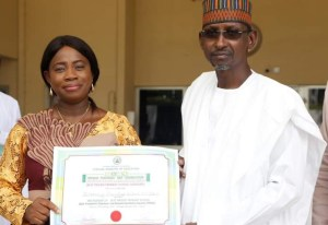 School Proprietress present certificate to FCT minisiter, Muhammad Musa Bello, as they 3rd best winner of Private schools in Nigeria  during the celebration of the world Teachers Day
