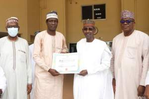 Minister of the FCT, Muhammad Musa Bello (m) receives certificate from the principal of GSS Kubwa, who emerged as the overall winner as the best School Administrator during the celebration of world Teachers Day.
