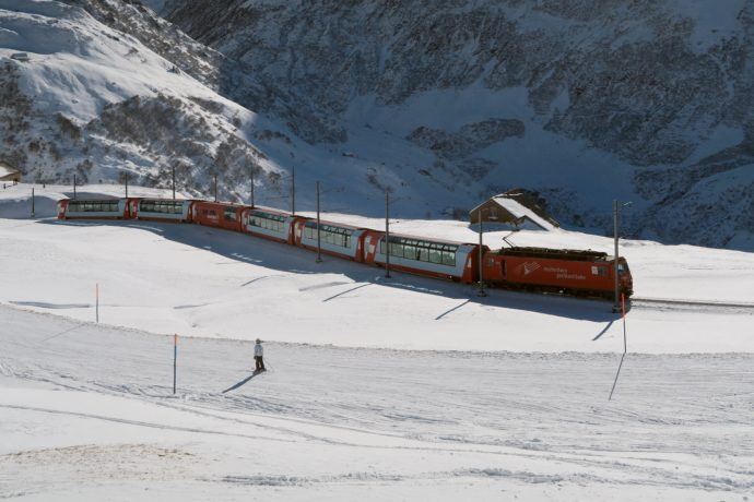 A skier looks at the passing Glacier Express. Photo Credit: Kecko/Flickr