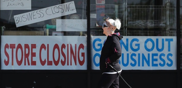 a woman front of store closing sign