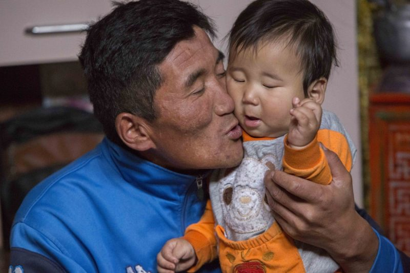 Jargalsaikhan Erdene-Bayar holds his eight-month-old son Munkh-erdene inside his family's ger in Ulaanbaatar. Erdene-Bayar herded livestock in the countryside until a harsh winter killed most of his animals and forced him to look for work in the city. Credit: Anne Bailey