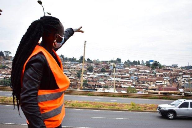 La journaliste Asha Jaffar, en gilet réfléchissant orange, montre l'étendue du quartier informel de Kibra à Nairobi, depuis une route avoisinante.