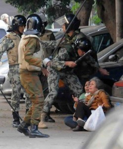 An Egyptian soldier is seen attacking an elderly woman in this photograph