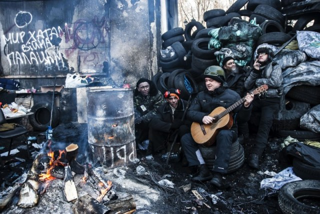 Euromaidan protesters sing songs as they warm by the fire barrels near the barricades on Hrushevskoho Street in Kiev, Ukraine on 2 February, 2014. Copyright Demotix