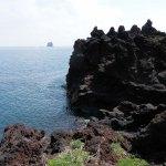 Stromboli, coulée de lave atteignant la mer avec en fond, une île constituée par une ancienne colonne de lave
