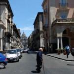 Catane, un viel homme traverse une rue avec le Duomo en fond