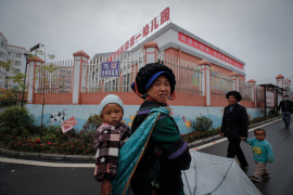 Ethnic minority women walk with their children near a kindergarten with a banner that reads 'I'm a China doll, can speak Mandarin' at the apartment houses compound built by the Chinese government in Yuexi county, southwest China's Sichuan province on Sept 11, 2020 [Andy Wong/AP Photo]
