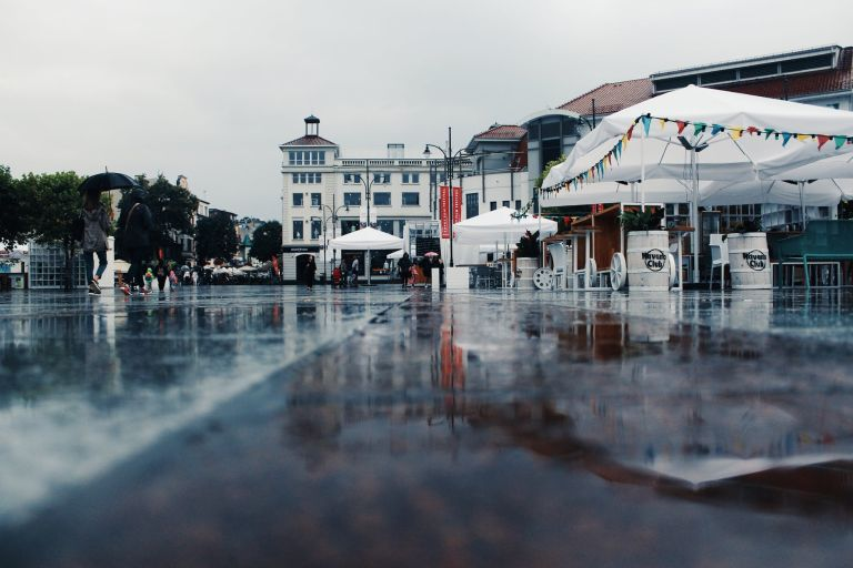 people walking near tents during rain